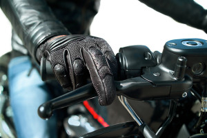 Closeup of the Hand of motorcyclist in protective glove on a throttle control, isolated on white